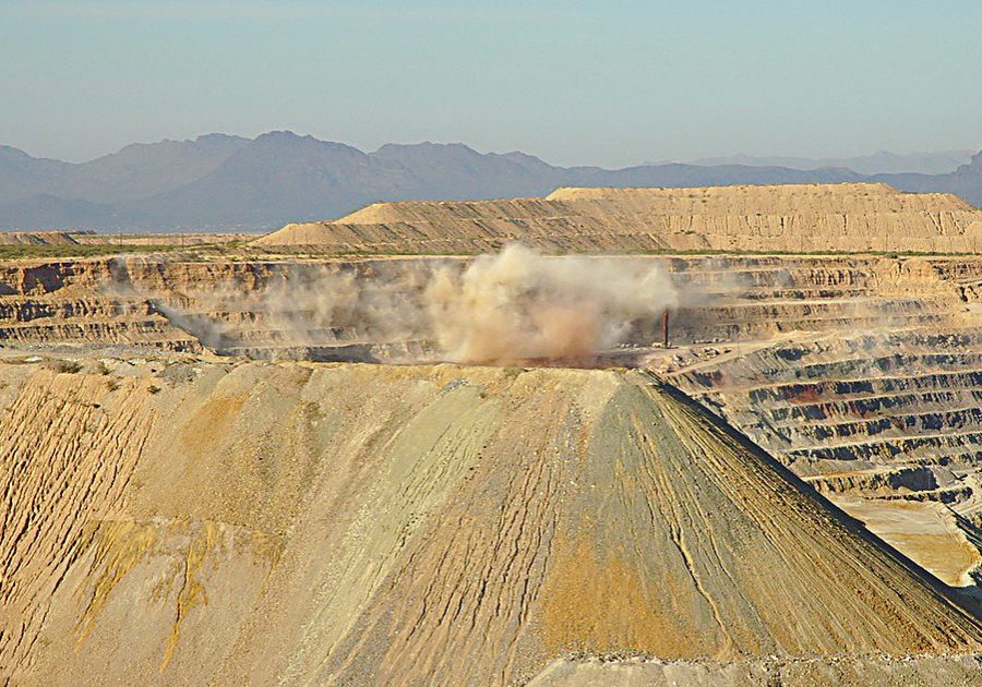 "Planned explosion during mining operations at the Freeport-McMoran copper and gold mine in Green Valley, Arizona. Mines like this produce toxic, sludgy waste — called ""tailings"" — that need to be stored safely to prevent water-table contamination. (Photo credit: Burley Packwood/Wikimedia Commons)"