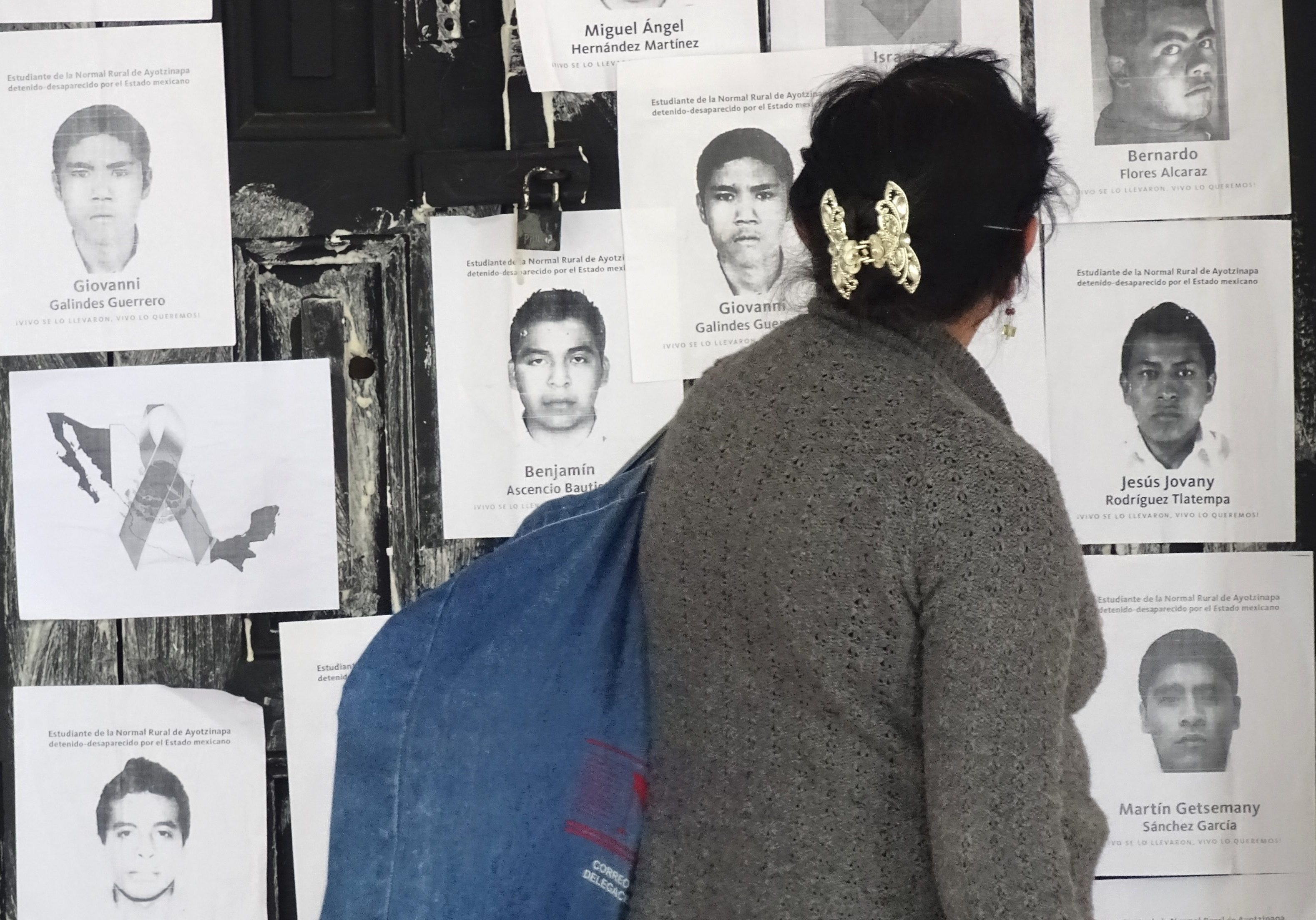 Woman Walks Past Protest Posters for Disappeared 43 Students from San Cristobal de las Casas, Chiapas, Mexico. Source:  Credit: Adam Jones/Wikimedia Commons
